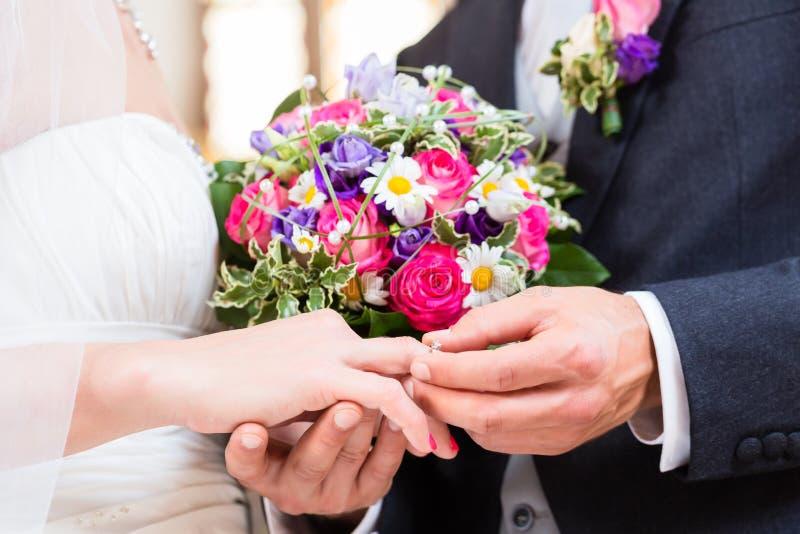 修饰在新娘的手指的滑动环在婚礼 图库摄影