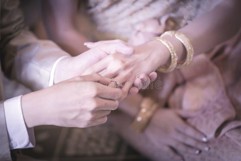 修饰在新娘的手指的滑动环婚礼的 免版税图库摄影