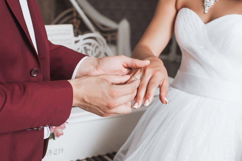 修饰安置婚戒在他的新娘的手指在仪式期间 免版税库存图片
