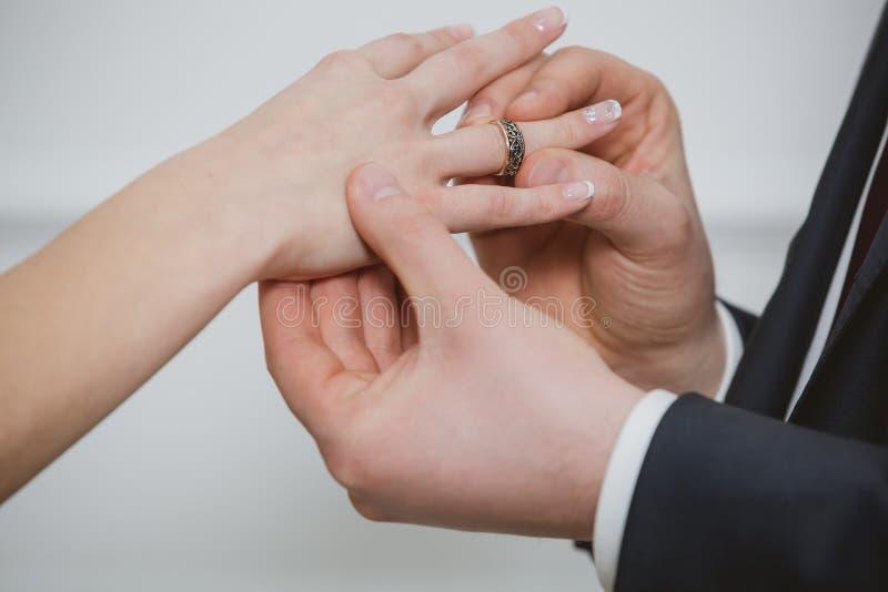 修饰把圆环放在他可爱的妻子的手指上 免版税图库摄影