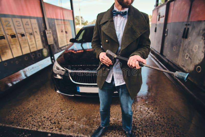 修饰的人摆在与水管在车洗涤的驻地在他的汽车附近 库存照片