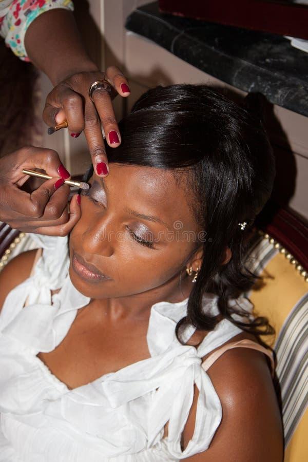 修饰非裔美国人的新娘构成的化妆师 免版税图库摄影