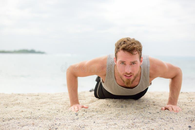 俯卧撑crossfit人在海滩的健身训练 免版税库存照片