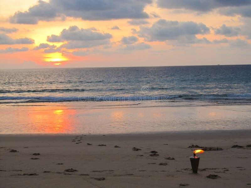 俯视在一个浪漫海滩的吻合风景灼烧的火炬在日落 免版税库存照片