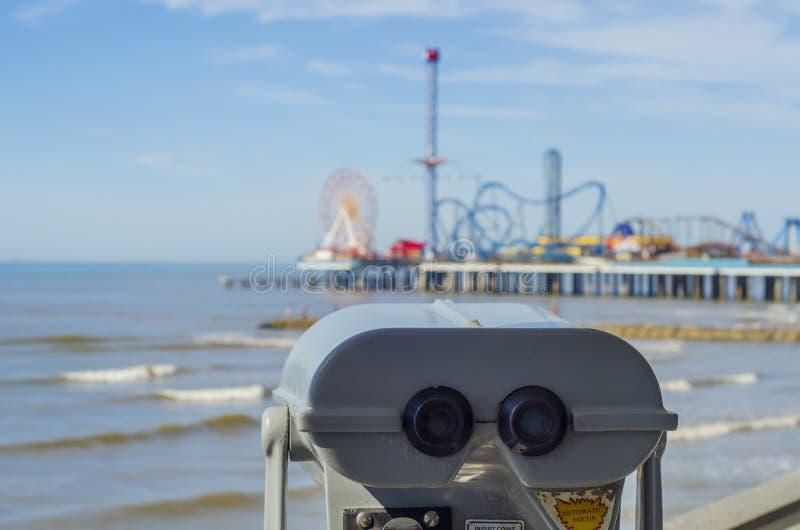 俯视海滩和码头的投入硬币后自动操作的双筒望远镜 免版税图库摄影