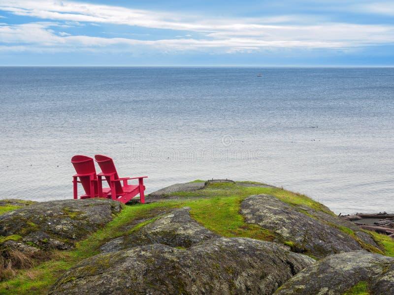 俯视海洋岸的两把椅子 免版税图库摄影