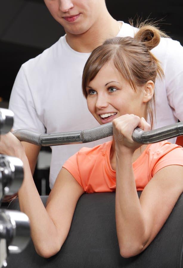 俱乐部健身女孩她的培训人 免版税库存照片