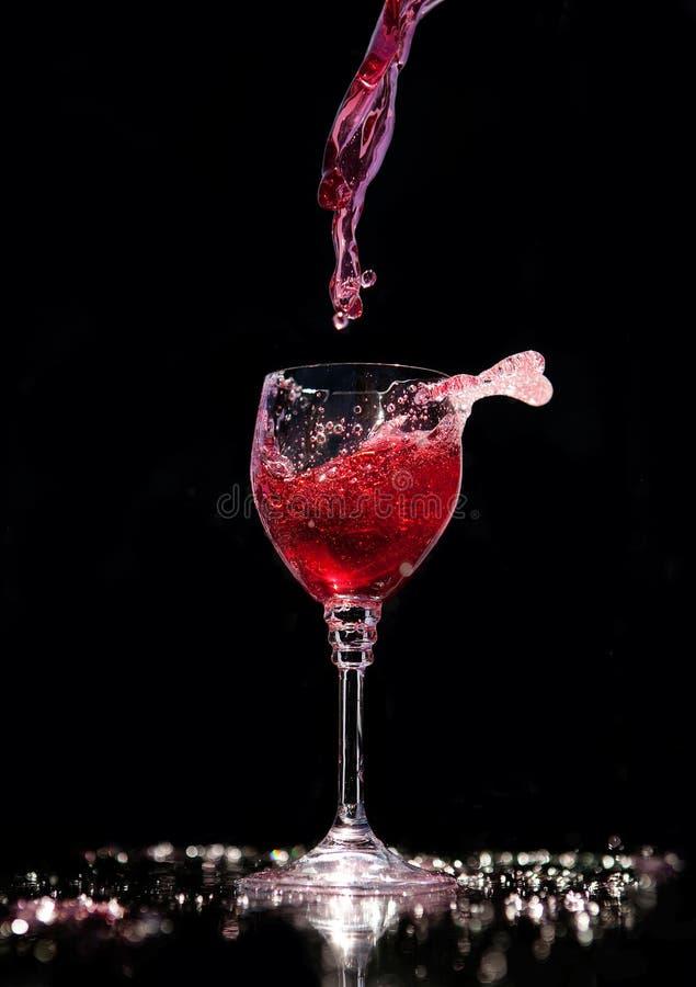 倒一杯在黑背景的红葡萄酒 免版税库存照片