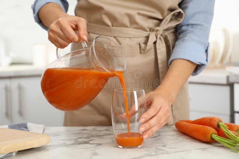 倒从水罐的妇女鲜美红萝卜汁入玻璃在桌上户内 库存照片