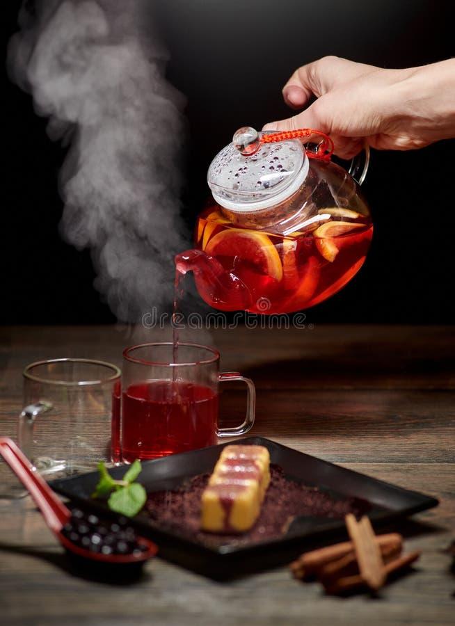 倒从玻璃水壶的手热的茶 蒸在玻璃的茶 在黑暗的背景的可口日本甜点心 免版税库存图片