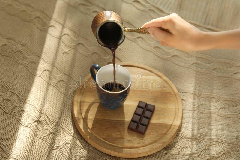 倒从cezve的年轻女人热的咖啡入在床上的杯子 免版税库存照片