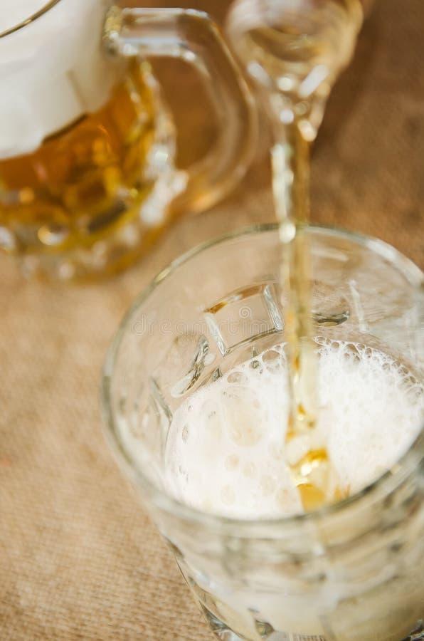 倒啤酒入从瓶的一块玻璃 库存图片