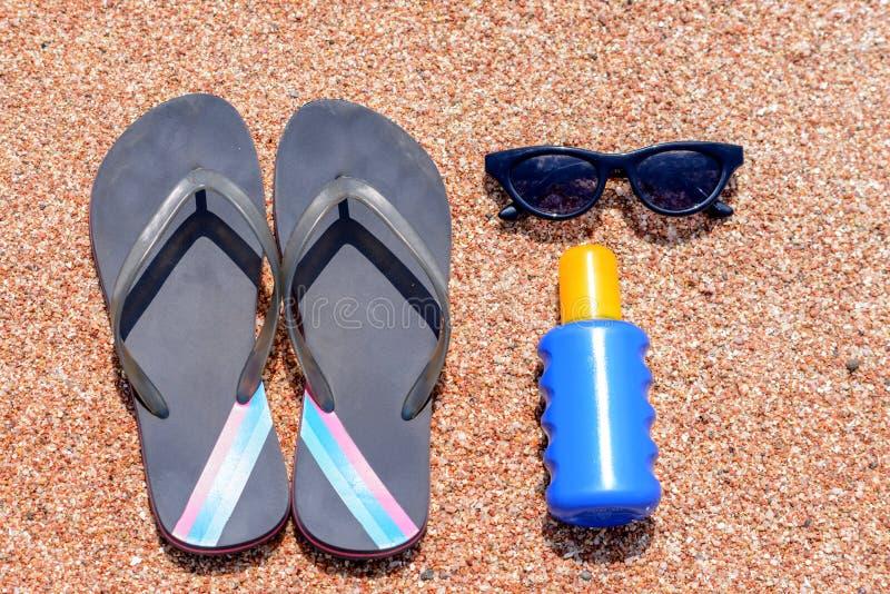 滑倒在海滩的外衣遮光剂和太阳镜 库存照片