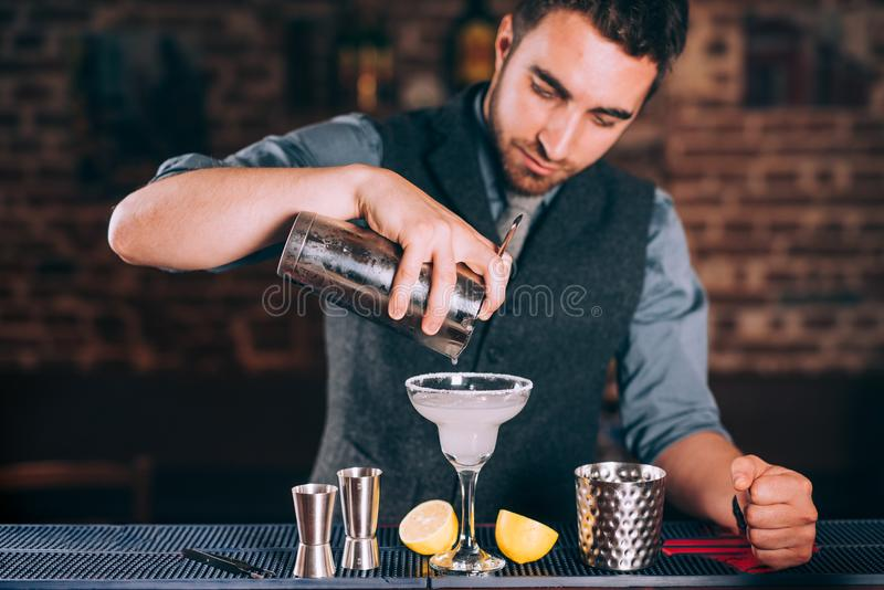 倒在玻璃的男服务员画象新鲜的石灰玛格丽塔酒在餐馆 免版税图库摄影