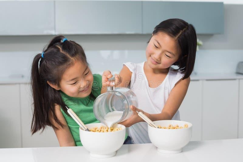 倒在碗的两个愉快的女孩牛奶在厨房里 免版税库存图片