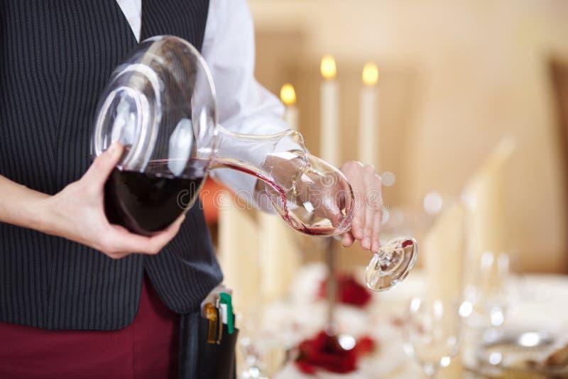 倒在葡萄酒杯的女服务员红葡萄酒 免版税库存照片