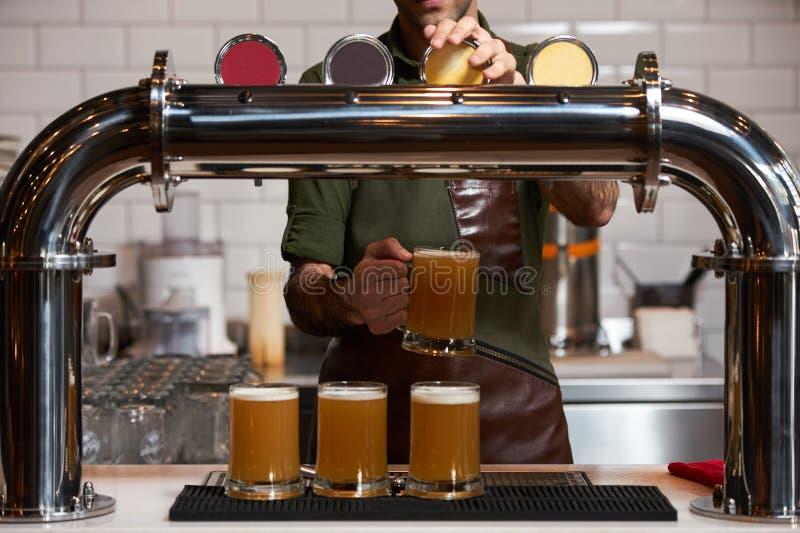 倒新鲜的啤酒的侍酒者入啤酒杯在酒吧柜台,特写镜头 库存图片