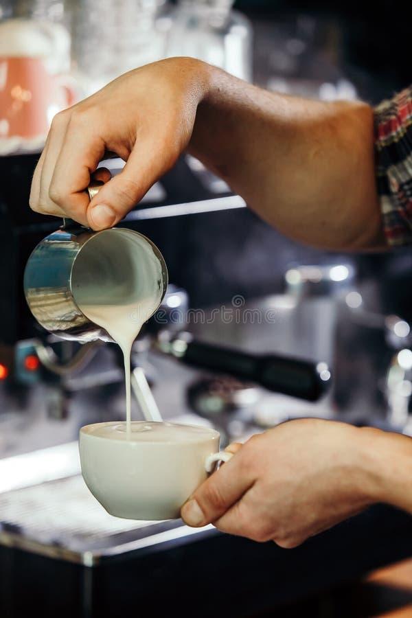 倒牛奶的侍者手做热奶咖啡 免版税库存照片