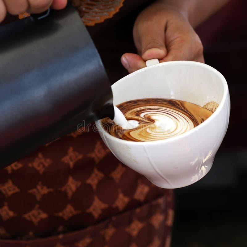 倒牛奶的女服务员手做热奶咖啡 图库摄影