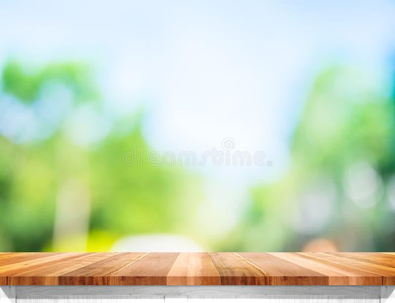 倒空与太阳的棕色木台式并且弄脏绿色树bokeh ba 库存图片