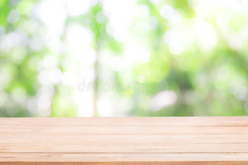 倒空与Defocus自然绿色bokeh,抽象nat的木桌 免版税库存照片