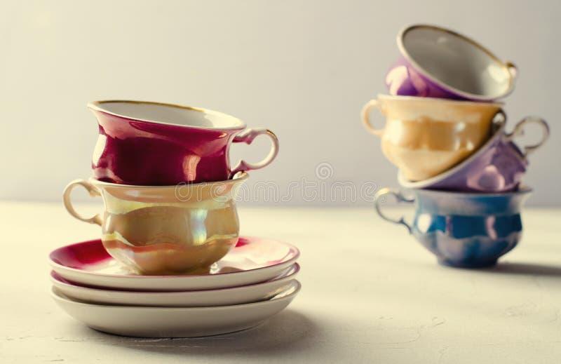 倒空五颜六色的瓷碗筷、杯子和板材在丁香,灰色背景 库存图片