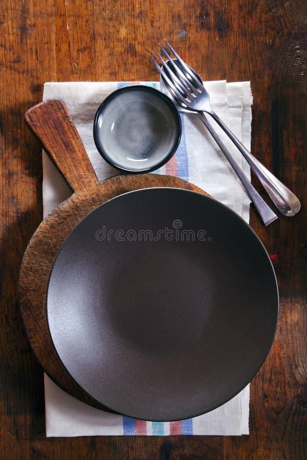 倒空在一块毛巾的黑碗在木纹理背景 Spac 库存图片