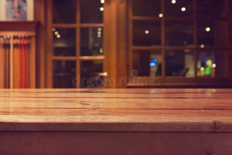 倒空在内部餐馆和酒吧bokeh背景的木甲板桌 免版税库存照片