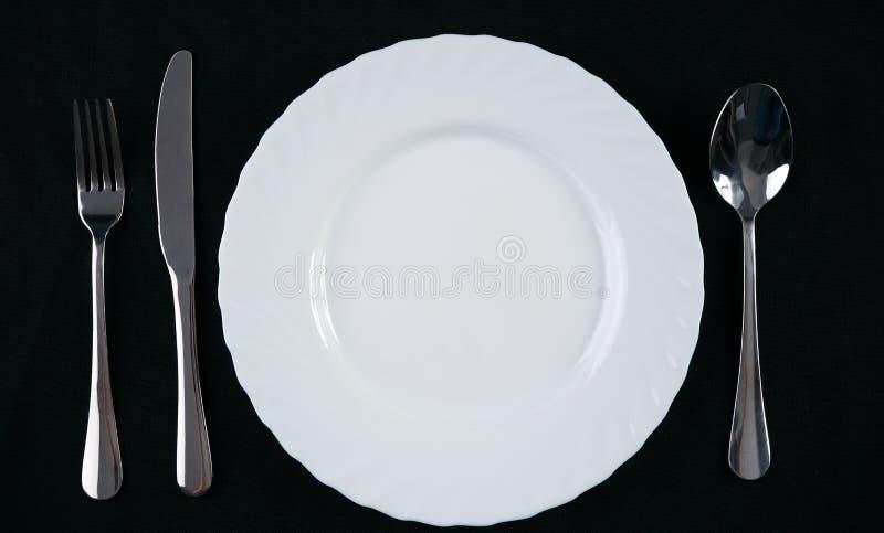倒空有银色叉子、在黑背景隔绝的刀子和匙子的白色板材 正餐餐位餐具 顶视图 库存照片