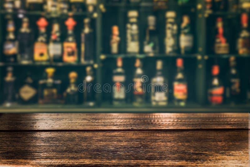 倒空木桌上面与被弄脏的逆酒吧的并且装瓶背景 图库摄影