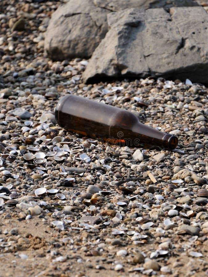 倒空水搁浅的棕色啤酒瓶在岩石、河淡菜小卵石和壳的环境里,在海滩的沙子  库存图片