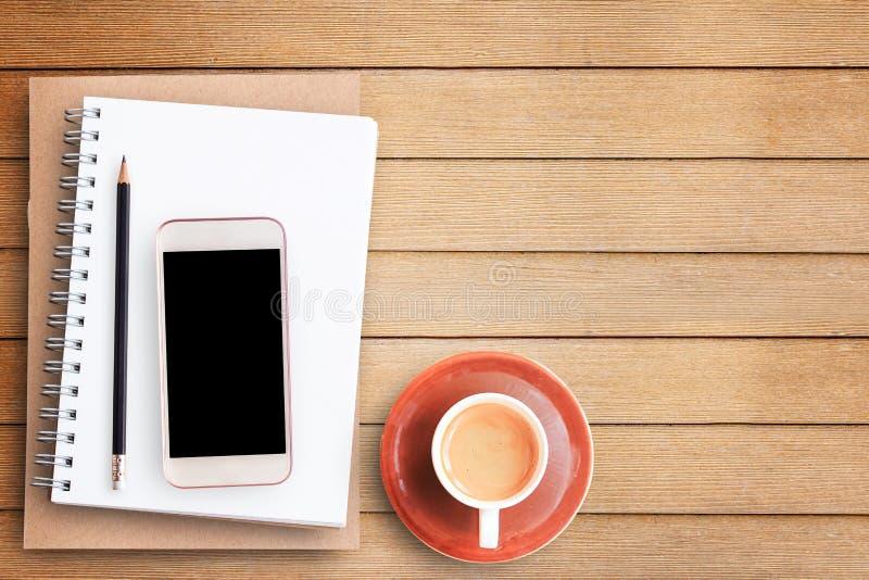 倒空白纸笔记本和巧妙的电话在棕色木桌上 库存图片