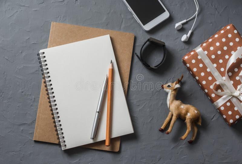 倒空空白的笔记本,礼物盒,圣诞节装饰驯鹿,在办公室桌面视图的电话 免版税库存图片