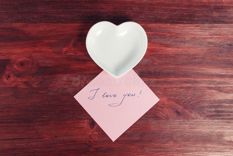 倒空陶瓷茶碟以心脏的形式和在一张黑暗的木桌上的笔记`我爱你` 免版税库存图片