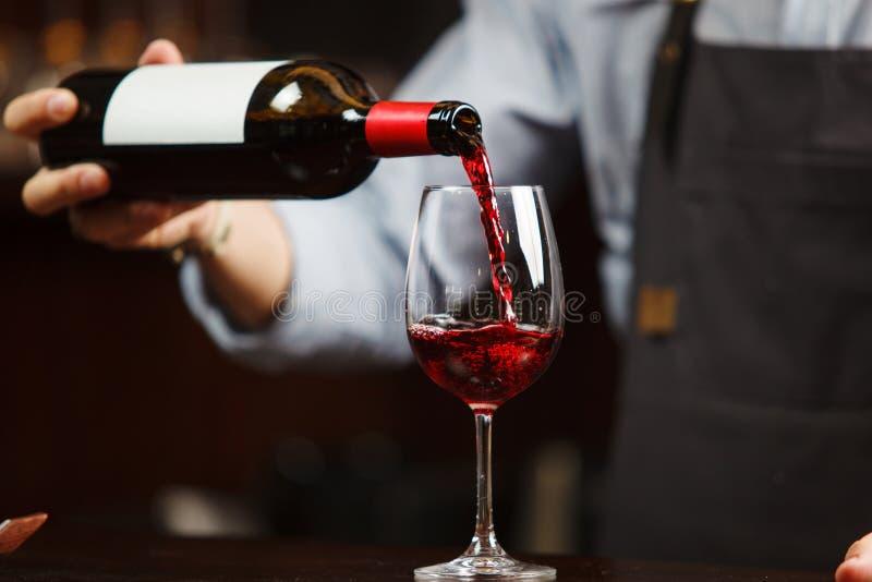 倒红葡萄酒的侍者入葡萄酒杯 斟酒服务员倾吐酒精饮料 免版税库存图片