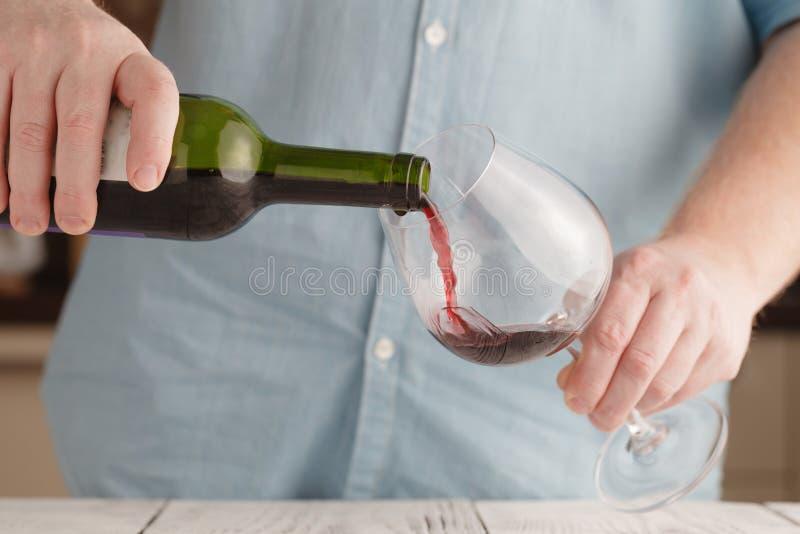 倒红葡萄酒的男性手入玻璃,特写镜头 免版税库存图片
