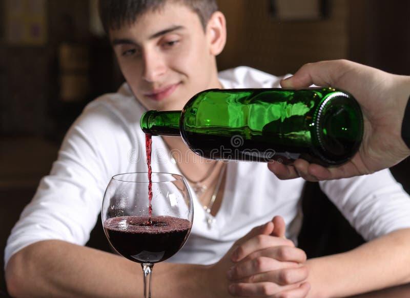 倒红葡萄酒的男服务员或侍者 免版税库存照片