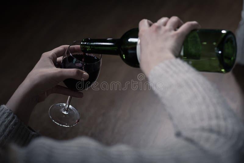 倒酒的酒客的手 库存图片