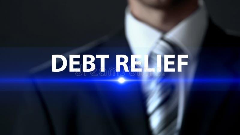 债务减免,站立在屏幕,经济援助前面的商人 库存照片