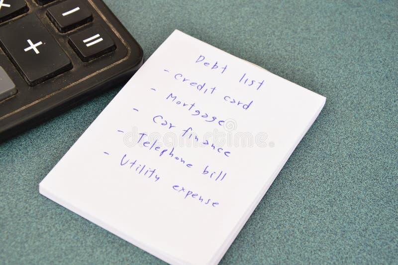 债务名单和计算器在桌上 库存图片