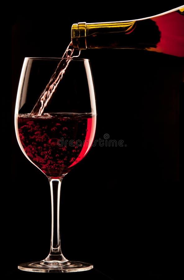倾倒一杯在黑背景之上的红葡萄酒 免版税库存图片