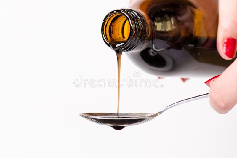 倾倒在匙子之上的瓶液体 背景查出的白色 药房和健康背景 医学 咳嗽和冷的药物 免版税库存图片