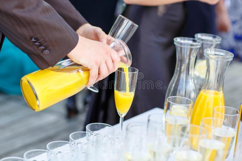 倾倒在婚礼之上的一个人的手橙汁 免版税库存图片