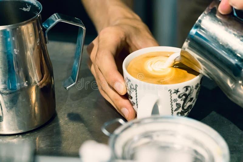 倾倒在杯子之上的Barista手热的牛奶做拿铁艺术 图库摄影