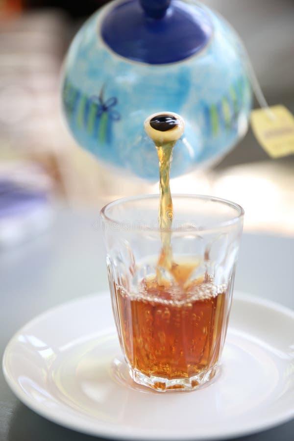 倾倒在茶杯之上的热的茶罐 免版税库存照片
