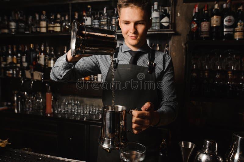 倾倒在酒吧柜台之上的年轻男服务员清楚的酒精饮料 免版税库存照片