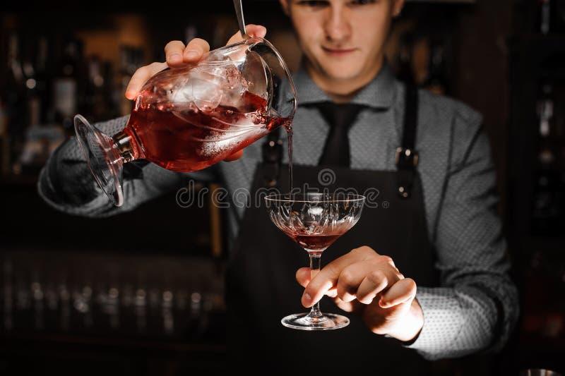 倾吐一个新鲜的酒精鸡尾酒的年轻男性男服务员入鸡尾酒杯 免版税库存图片