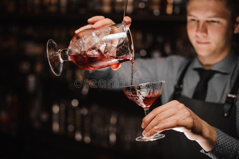 倾吐一个新鲜的酒精鸡尾酒的年轻男服务员入鸡尾酒杯 免版税库存图片