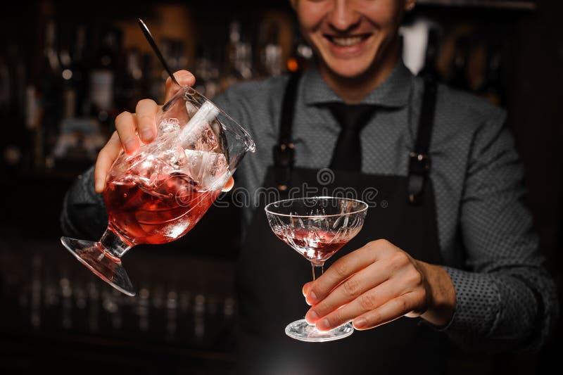 倾吐一个新鲜的酒精鸡尾酒的微笑的男服务员入鸡尾酒杯 库存图片