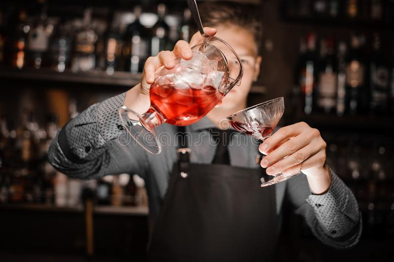 倾吐一个新鲜的酒精鸡尾酒的男服务员入鸡尾酒杯 免版税库存照片